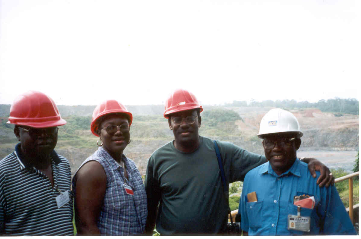 From L. to R. Edwin Omaboe , Dr. Angelina Ulzen-Chela, & Dr. Thad Ulzen  of Elwin International on tour at Damang Gold mine, Oct. 2001.Safety Engineer Mr. Francis Clement on R.